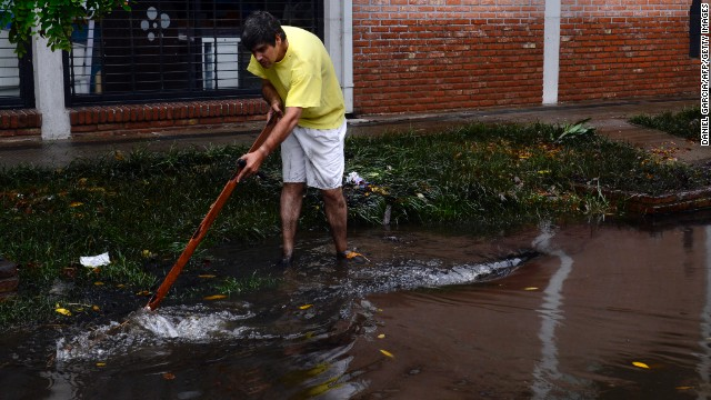 A man tries to drain water from a flooded street in La Plata on April 3.
