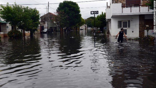 "A man wades through a flooded street on April 3 in La Plata. ""This storm is a catastrophe without precedent,"" said Santiago Martorelli, cabinet chief of the city."