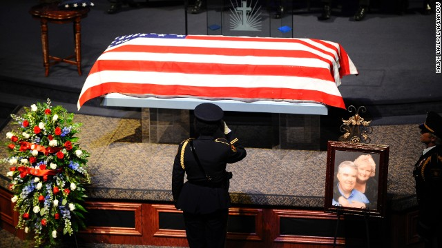 An officer salutes the casket during a memorial service for District Attorney Mike McLelland and his wife, Cynthia, on Thursday in Sunnyvale, Texas.