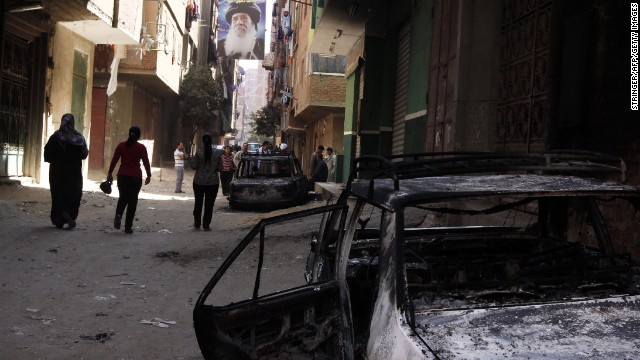 A portrait of a past Coptic pope hangs above a burnt-out car after clashes between Christians and Muslims in Khosous, Egypt.