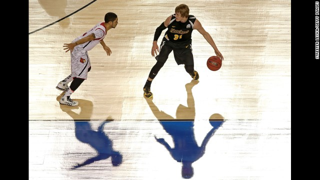 Ron Baker of Wichita State runs the offense as Peyton Siva defends.