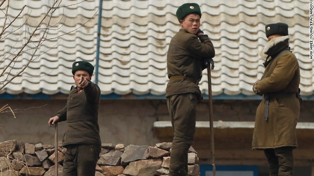 A North Korea soldier gestures to stop photographers from taking photos from a Chinese tour boat as other soldiers look on along the North Korean bank of the Yalu River near the town of Sinuiji across the Chinese city of Dandong in Liaoning province, China, on Saturday, April 6.