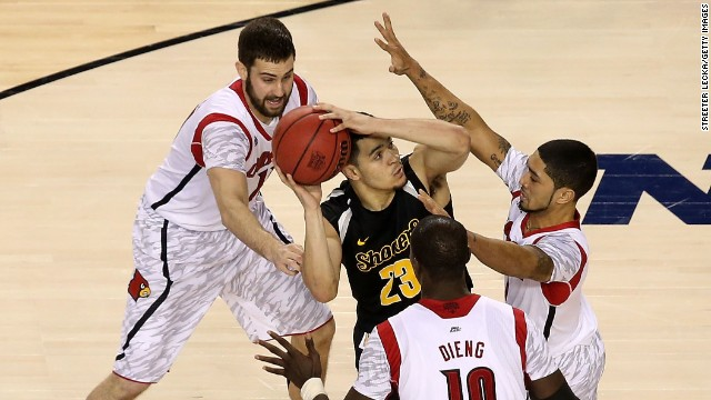 Fred VanVleet of Wichita State looks for a shot against Luke Hancock, left, Peyton Siva, right, and Gorgui Dieng, center, of Louisville.