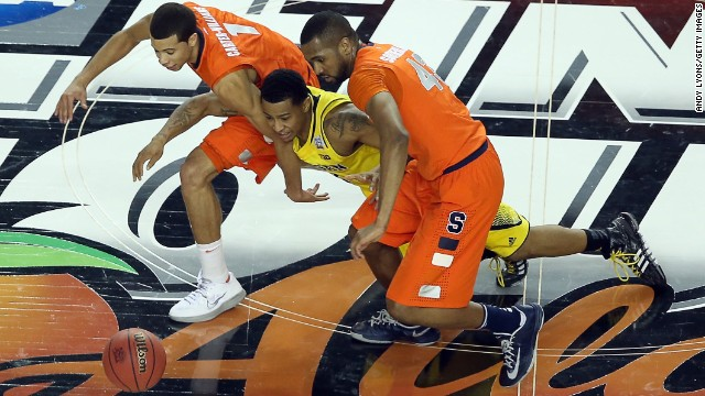 Trey Burke of Michigan chases down a loose ball against Michael Carter-Williams, left, and James Southerland, right, of Syracuse.