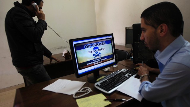 Palestinians look at a picture depicting the '#Op_Israel' campaign launched by Anonymous in Gaza City on Sunday.
