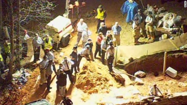 Rescuers try to save two young children buried