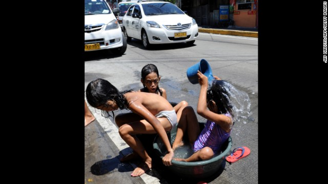 Children cool off in a tub on a scorchingly hot day in a slum in Manila, Philippines, on Saturday, April 6.