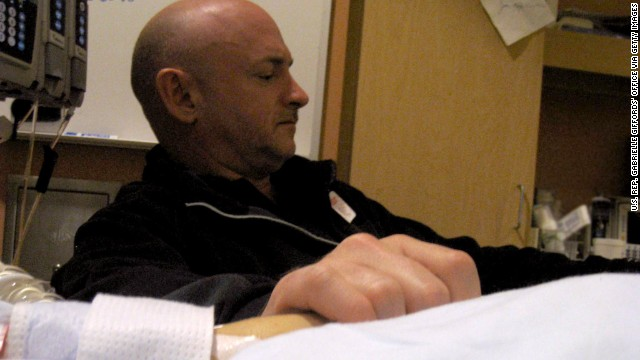Giffords' husband, Mark Kelly, holds his wife's hand in her hospital room at the University Medical Center in Tuscon on January 9, 2011.