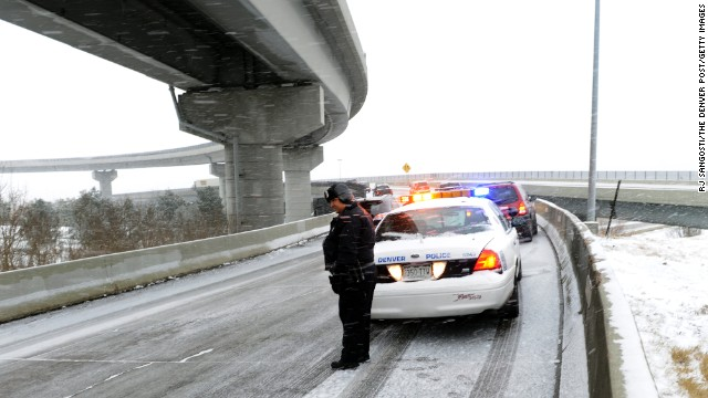 Police officer Adolph Chavez waits for tow trucks after cars became stuck on a ramp to Interstate 70 during a snowstorm in Denver on April 9. 