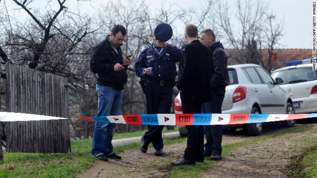 Serbian police officers guard the entrance to a yard in the village of Velika Ivanca on Tuesday.