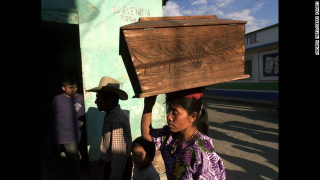 A Mayan woman carries a coffin in 2002 bearing remains of one of 100 Mayans massacred in Zacualpa, Guatemala. The victims were finally laid to rest years after they were bludgeoned, shot or hacked to death.