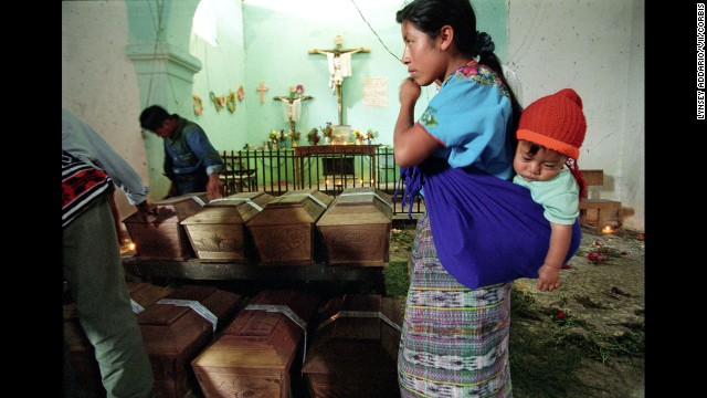 At a Guatemalan church in Rabinal in 2002, a grieving mother stands over the remains of her daughter, a victim of a massacre conducted by the army in 1982. Coffins bearing victims' remains were brought to the church months after archeologists found and exhumed the bodies based on witness testimony.