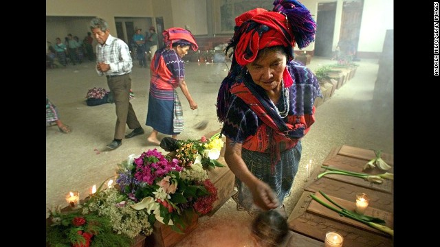 A Mayan woman burns incense over victims' coffins before a funeral in April 2002 in Zacualpa, Guatemala.