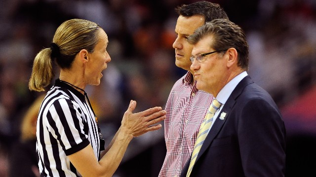 Head coach Geno Auriemma of the Connecticut Huskies and head coach Jeff Walz of the Louisville Cardinals speak to an official after a flagrant foul call during the game on April 9.
