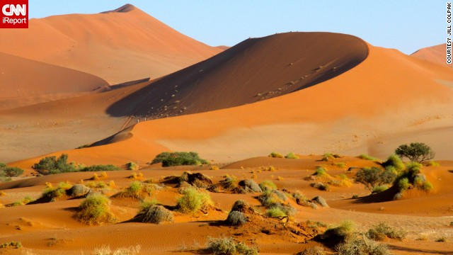 The morning sun casts a glow over the sand dunes of Namibia.