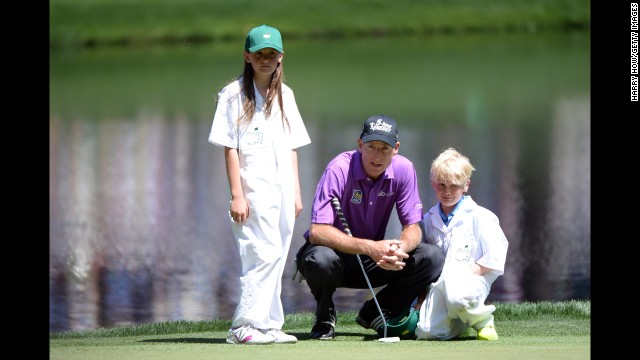 Jim Furyk of the U.S. lines up a putt with his children Caleigh and Tanner.