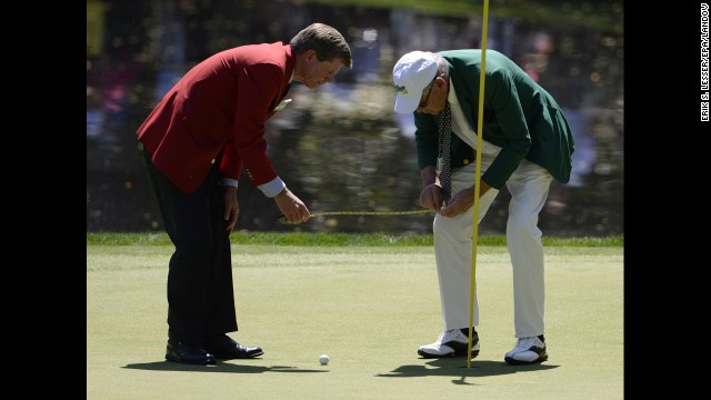 Officials measure how close a ball landed to the pin on the ninth hole during the Par 3 Contest.