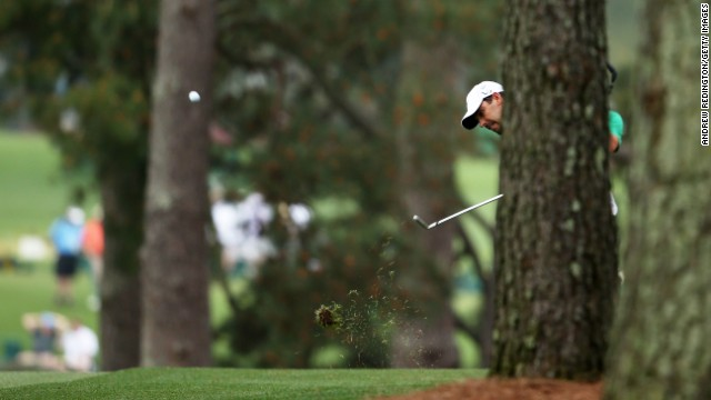 Charl Schwartzel of South Africa hits a shot from behind a tree on the first hole.