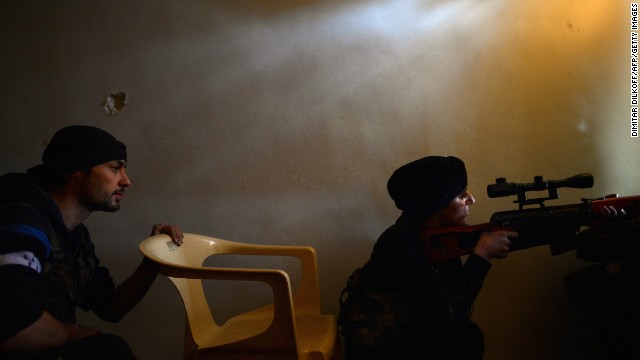 A female rebel monitors the movement of Syrian government forces in Aleppo's Sheikh Maqsud neighborhood on April 11.