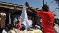 A man samples second-hand clothes (locally known as mitumba) at the Gikomba open-air market on June 25, 2012, in Nairobi. Local dealers welcomed Kenya's Finance minister Njeru Githai's move to lower import duty on ' Mitumba' in this year's budget read two weeks ago. However, trade experts say the reduction on import duty, will put over 270,000 jobs in the cotton industry at risk and lives of farmers as well.