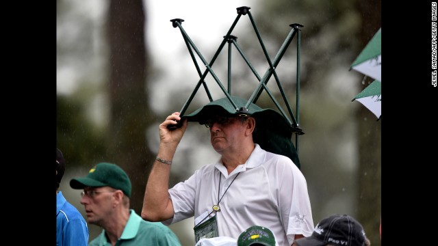 A fan takes cover in the rain during the second round on April 12.