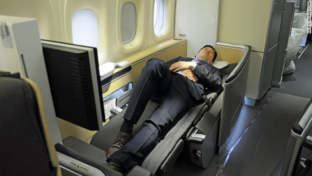 Our fill-in model demonstrates a fully reclined first-class seat. When properly set up for flight, there's a mattress on top of the seat. A partition can be raised between seats to increase privacy. We don't recommend sleeping in a business suit.