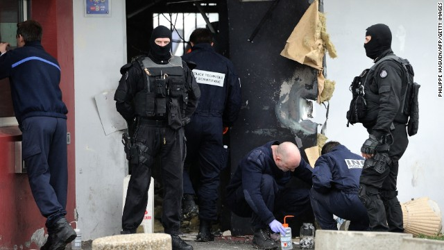 Police officers seek evidence around the destroyed door of the Lille-Sequedin penitentiary on April 13.