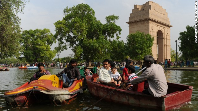 Families paddle boats on a pond near India Gate in New Delhi on Sunday, April 14. 