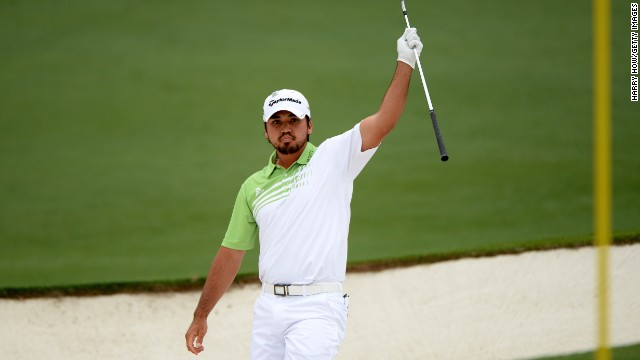 Jason Day of Australia lifts his club after hitting the ball out of the bunker for an eagle on the second hole.