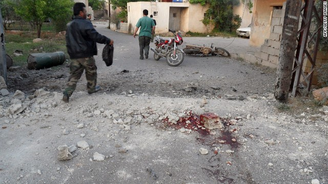 A man walks past bloodstains on a street in the Lebanese border town of Qasr on Sunday, after the shelling.