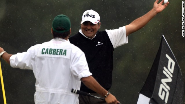 Angel Cabrera of Argentina smiles to his caddie and son Angel Cabrera Jr. after he sinks a birdie putt on the 18th.