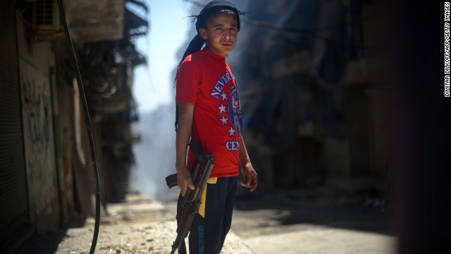 A Syrian boy holds an AK-47 assault rifle in the streets of Aleppo on Sunday, April 14.