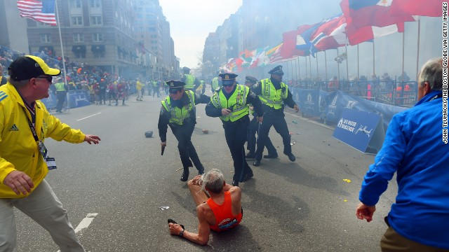 Police officers with their guns drawn hear the second explosion down the street. The first explosion knocked down 78-year-old runner Bill Iffrig at the finish line. He got up a few minutes later and finished the race.