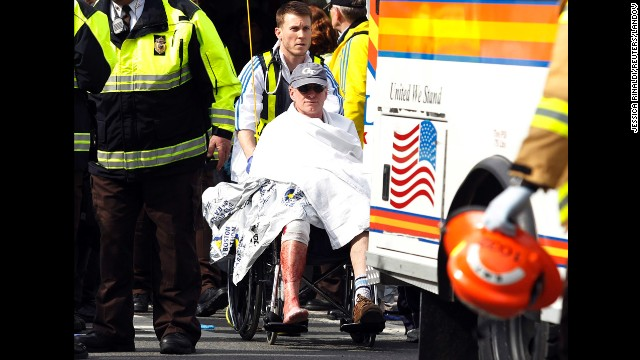 A runner in a wheelchair is taken from a triage tent after the explosions went off.