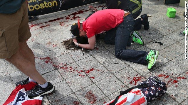 A man comforts a victim on the sidewalk at the scene of the first explosion April 15 near the finish line of the 117th Boston Marathon. The two explosions killed three people and wounded more than 170 others.