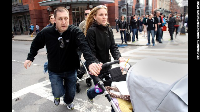 A couple runs from the scene pushing a stroller.