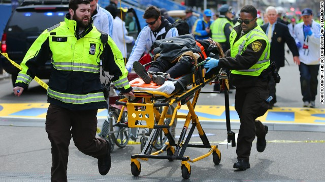 A bystander who was injured in the first explosion is wheeled across the finish line while receiving medical attention from rescue workers.
