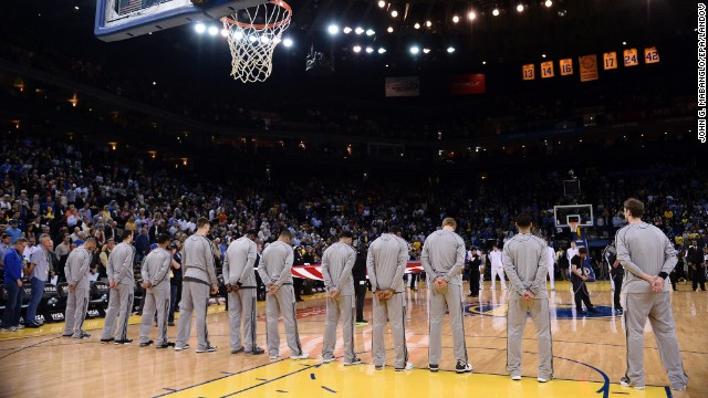 Players and fans observe a moment of silence before the San Antonio Spurs and Golden State Warriors NBA game in Oakland, California, on Monday.