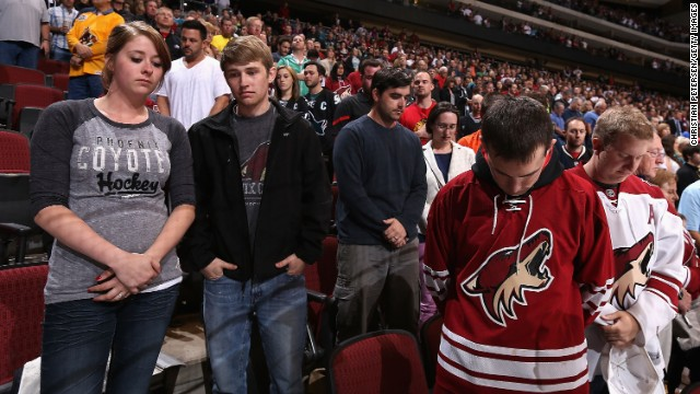Fans pause for a moment of silence before the NHL game between the Phoenix Coyotes and the San Jose Sharks on Monday in Glendale, Arizona. See the world reaction to the attack.