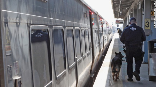 A police officer and his dog guard a Long Island Rail Road train at the station in Hicksville, New York, on Monday. See all photography related to the Boston bombings.