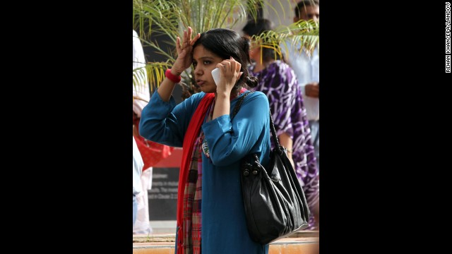 A woman talks on the phone after she was evacuated along with hundreds of other workers in Karachi.