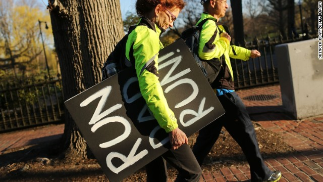 A woman carries a sign she made to support her runner husband near the scene of the bombings.