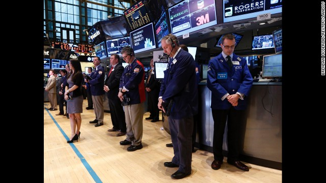 Traders observe a moment of silence on Tuesday before the opening bell on the floor of the New York Stock Exchange.