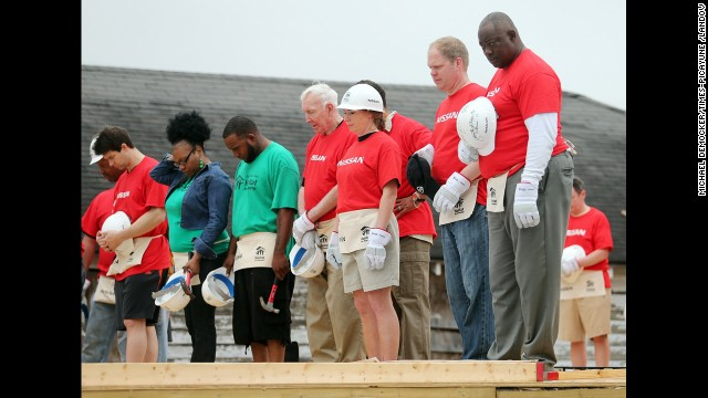 Several former Heisman Trophy winners, including former Saints running back George Rogers, right, observe a moment of silence for the bombing victims Tuesday before working on a Habitat for Humanity home in New Orleans.