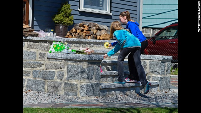 Two young girls leave flowers on the steps outside the home of 8-year-old Martin Richards, who was killed in one of the explosions at the marathon.
