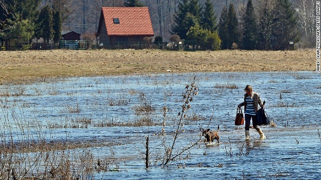 A woman and dog cross a flooded road in Zalubice Stare, Poland, on April 16.