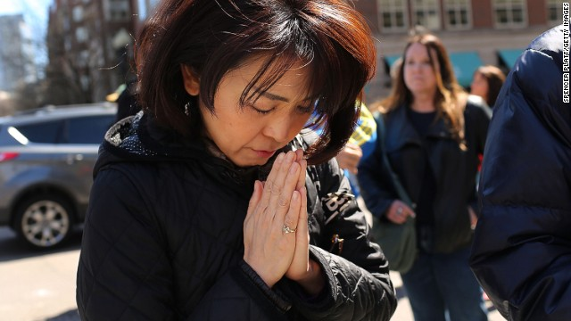 A woman prays at a security gate near the scene of the bomb attack where visitors have congregated on April 16. See the aftermath in Boston.