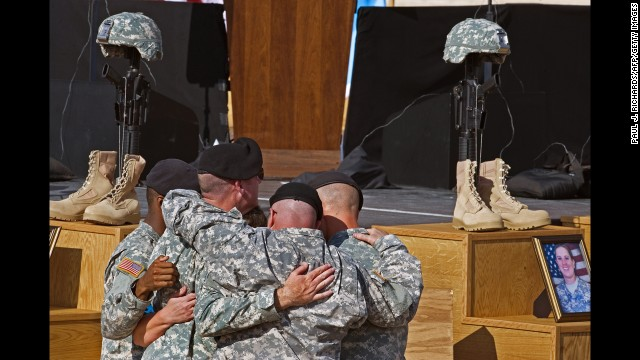 Soldiers comfort each other at the Fallen Soldier Memorial at Fort Hood, Texas, on November 10, 2009, during a ceremony honoring the 13 soldiers and civilians killed in a shooting rampage five days earlier.