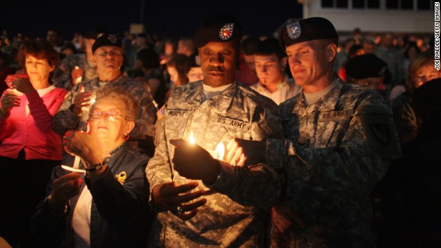 In the darkness of terror attacks, Americans find the light. Here, officers hold candles during a vigil for those killed at Fort Hood.