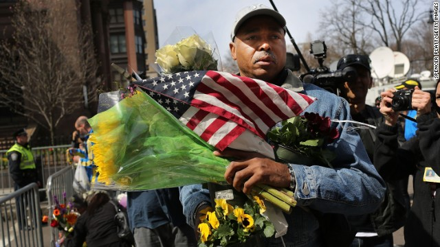 A man carries balloons, flowers and flags to a memorial for victims on April 16, just blocks from the scene of the bombings.